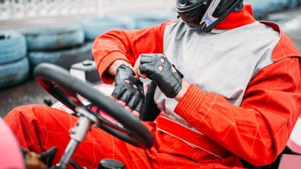Go-kart driver in helmet on karting speed track